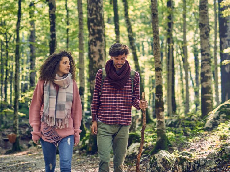 Man and Woman walk through the woods in fall