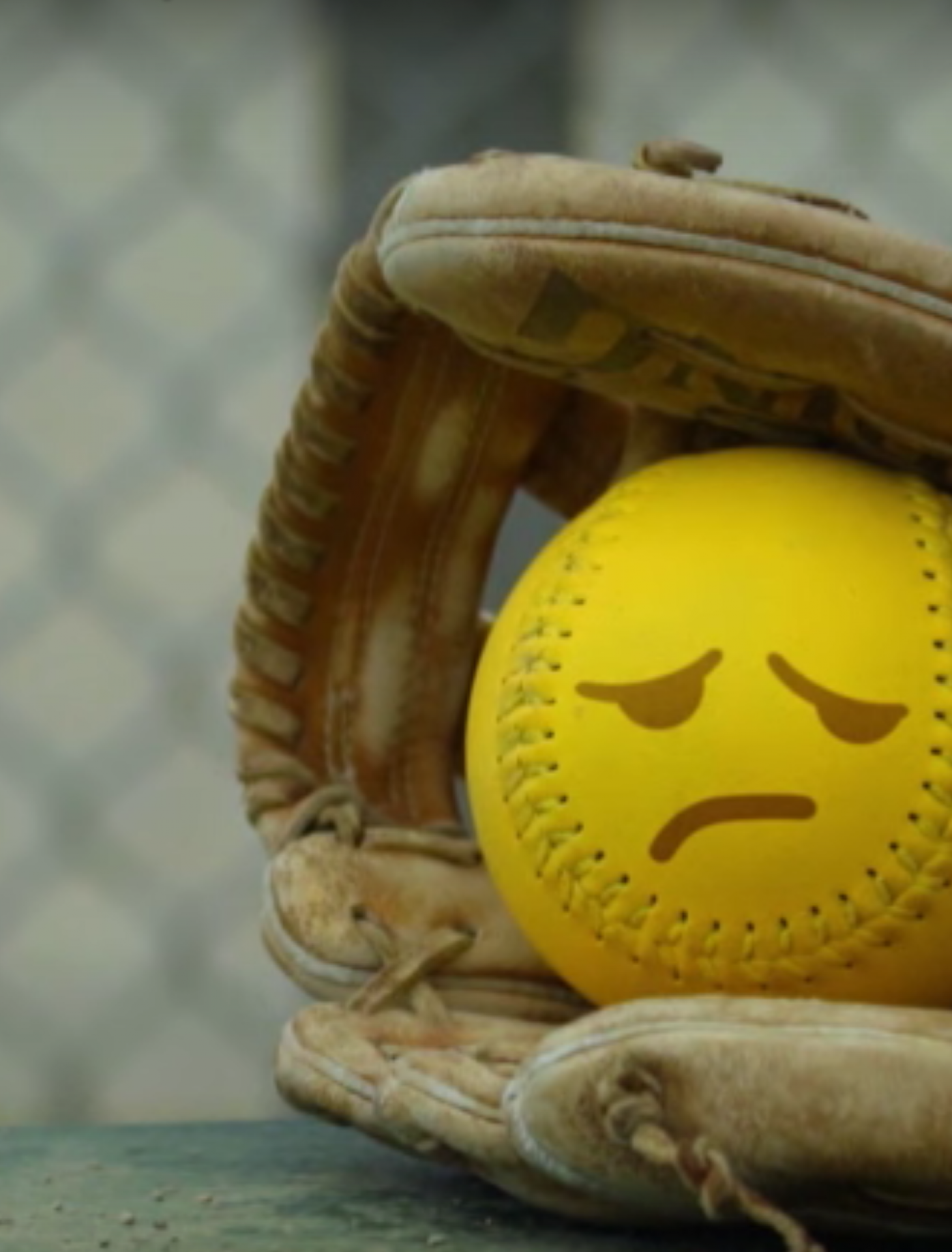still photo of a yellow baseball with sad face in a baseball glove